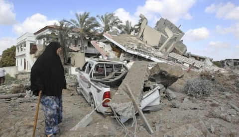 Palestinian woman walks past the remains of a house which police said was destroyed in an Israeli air strike in Gaza City